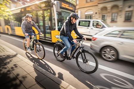 Zwei e-Bike Fahrer im regen Strassenverkehr