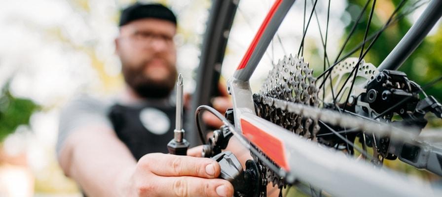 Mann schraubt am Hinterrad eines e-Bikes