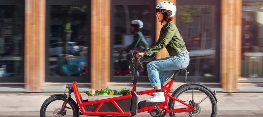 Frau transportiert ihren Einkauf im Lastenrad durch die Stadt