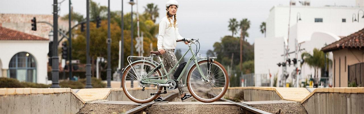 Frau mit Gazelle e-Bike am Bahnhof