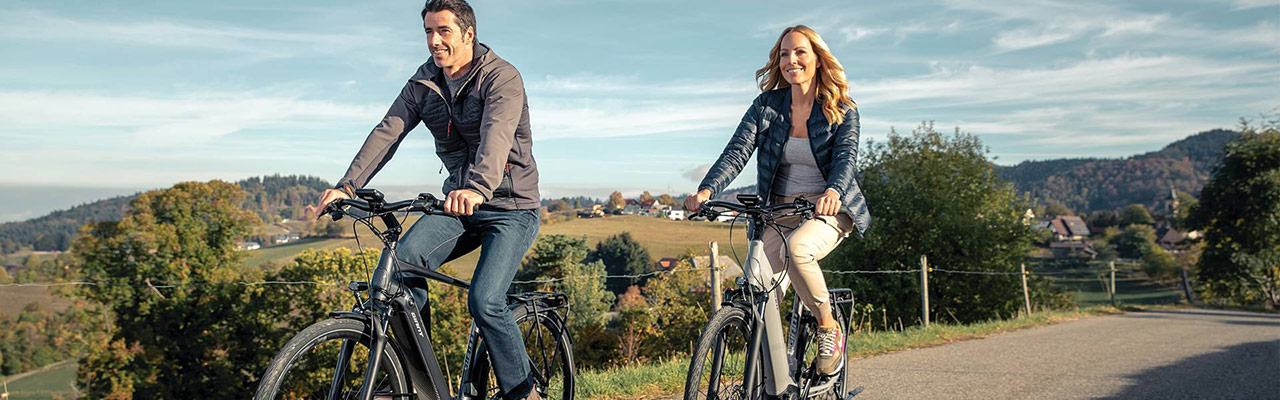 Zwei fröhliche e-Bike Fahrer in der Natur