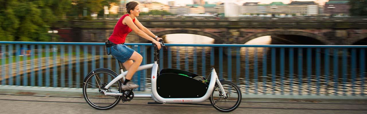 Eine Frau fährt auf einem Triobike Lasten e-Bike über eine Brücke