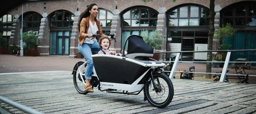 Frau fährt mit ihrem Kind im Urban Arrow Family durch die Stadt