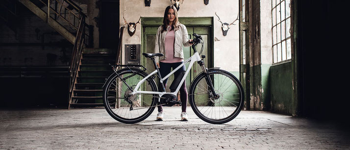 Frau hinter einem e-Bike mit Mixte Rahmenform von Riese und Müller