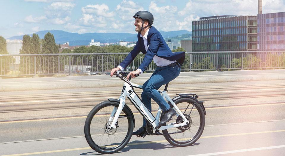 Ein Mann in Businesskleidung auf dem Speed Pedelec von Riese und Müller