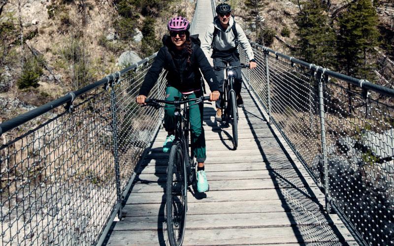 Zwei Personen fahren mit Trekking e-Bikes über eine Hängebrücke
