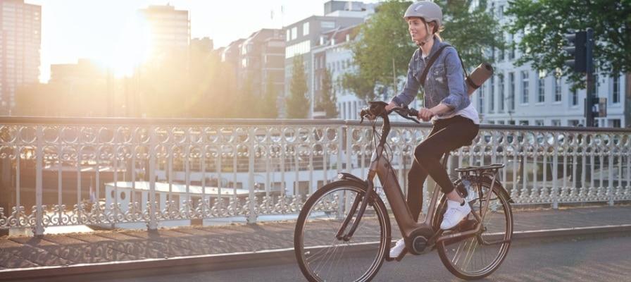 Frau fährt mit e-Bike auf einer Brücke.