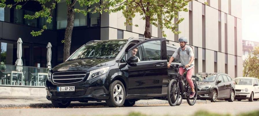 Auto mit mit offener Fahrertür parkt auf einer Straße und ein Mann fährt auf einem e-Bike darauf zu.