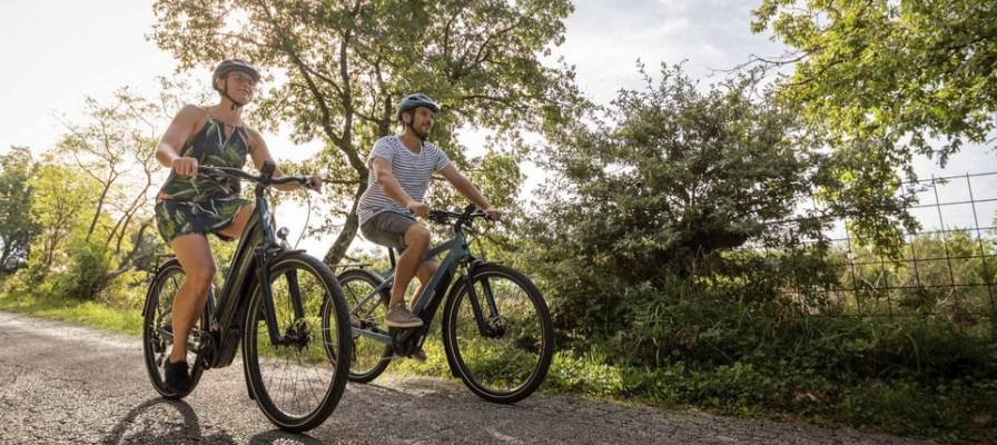 Mann und Frau fahren mit e-Bike auf asphaltierter Straße durchs Grüne.
