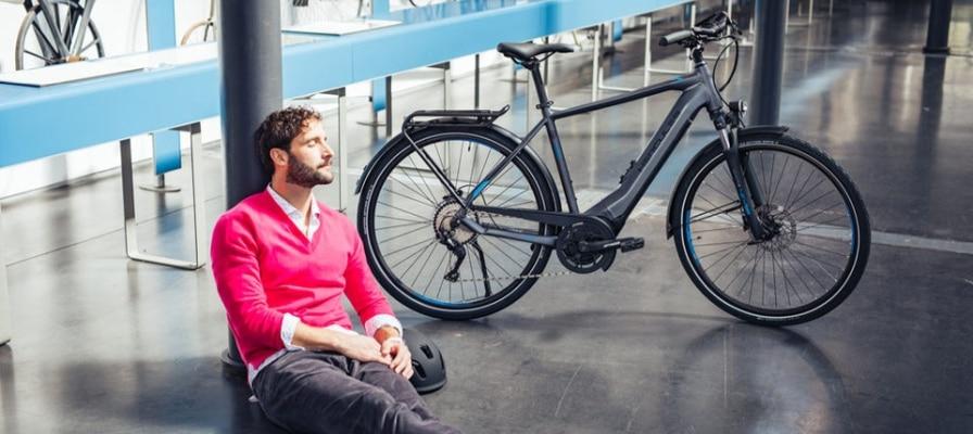 Mann sitzt auf dem Boden und sonnt sich, e-Bike steht daneben.