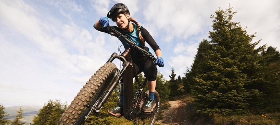 Frau in der Luft mit e-Mountainbike