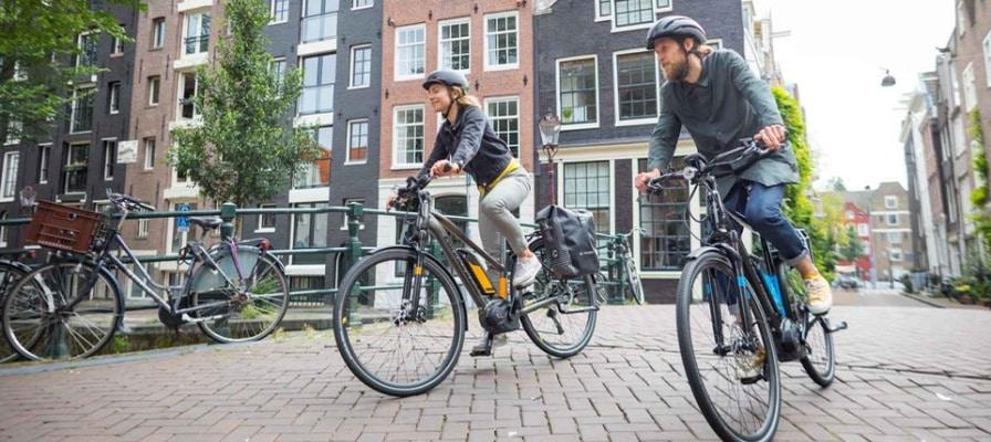 Mann und Frau mit e-Bikes unterwegs in der Stadt.