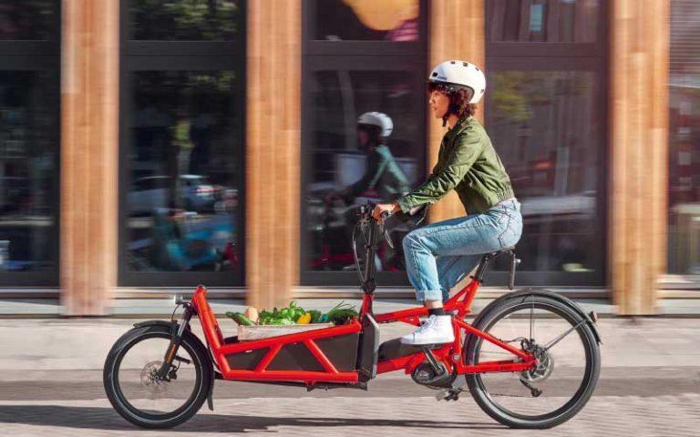 Frau faehrt mit rotem Riese und Mueller Lasten e-Bike durch die Stadt