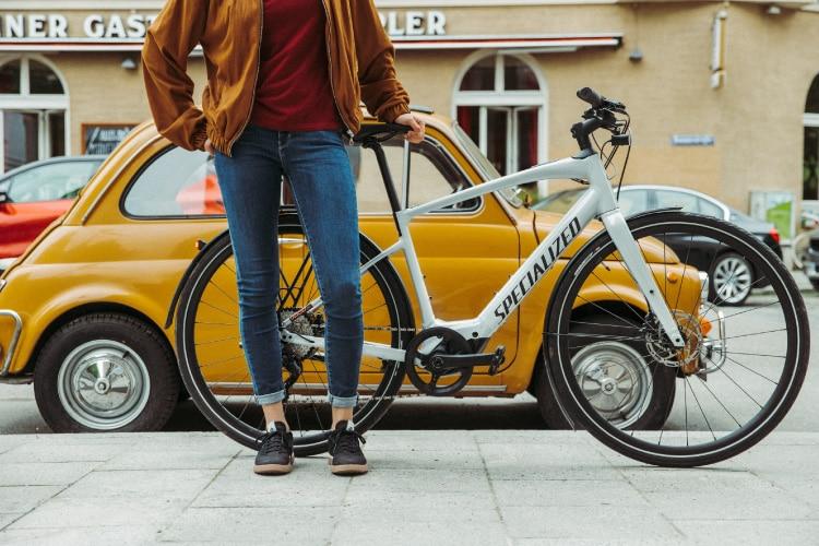 Frau steht mit einem Specialized e-Bike vor einem gelben Auto
