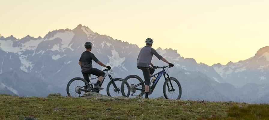 Zwei e-Mountainbike Fahrer stehen auf ihren Giant Trance X E+ vor einer Bergkulisse