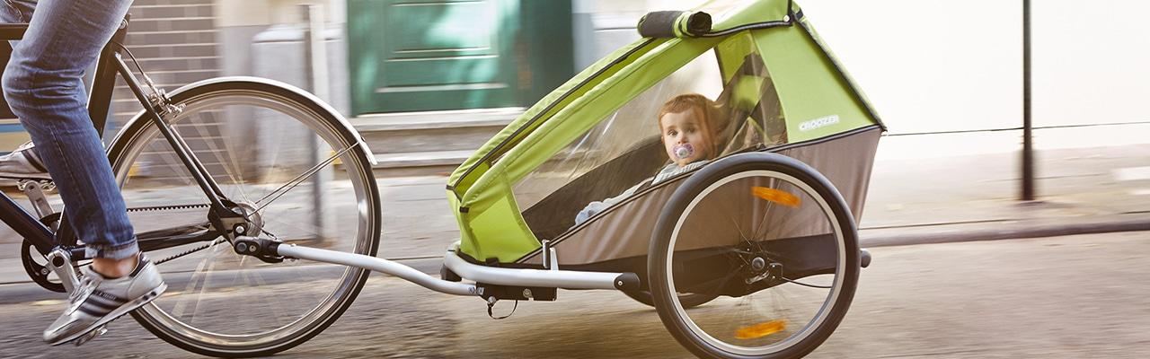 Frau auf e-Bike mit ihrem Kinderanhänger von Croozer