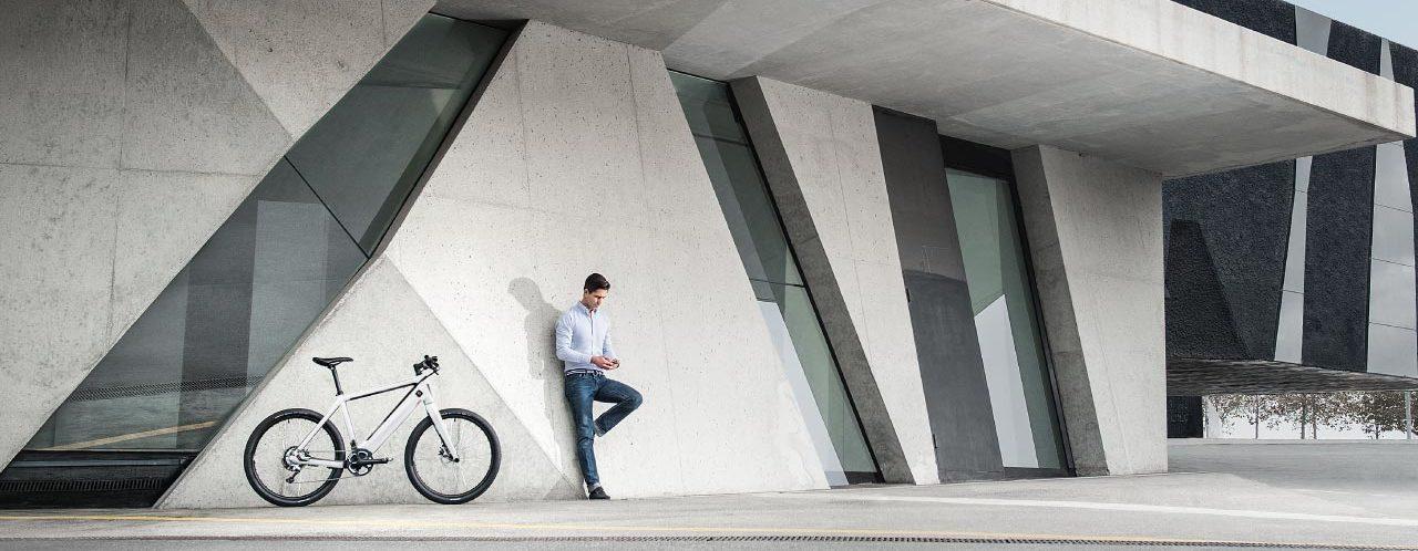 Mann schaut auf sein Smartphone neben seinem e-Bike