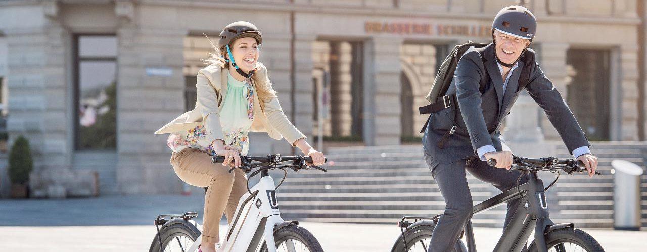 Mann und Frau in Businesskleidung auf ihren e-Bikes auf dem Weg zur Arbeit