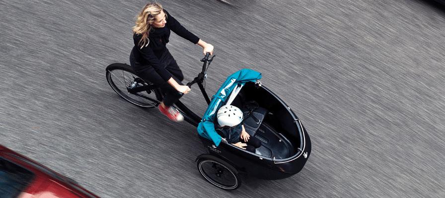 Frau fährt mit Kind in Triobike Lastenfahrrad durch die Stadt