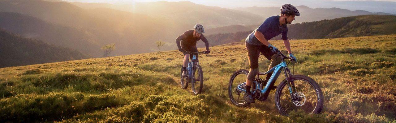 Zwei e-Mountainbiker fahren mit e-MTB Berg hoch
